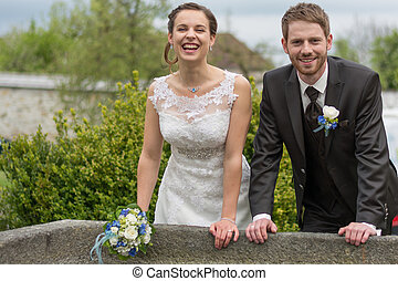 Newlyweds in old stone fountain