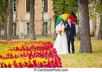 Newlyweds in the park with big umbrella