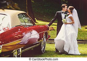 Newlyweds kiss behind an old American car