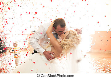 Newlyweds kiss passionate in the rain of red confetti