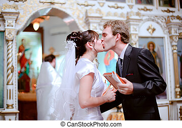 Newlyweds kiss.