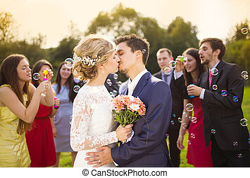 Young newlyweds kissing and enjoying romantic moment together at wedding reception outside, wedding guests in background blowing bubbles