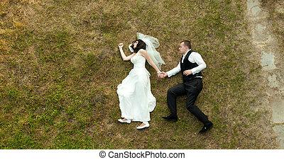 Newlyweds lie like walking on the grass