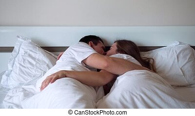 newlyweds, liggen in, bed, kussende , dekking, met, deken