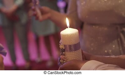 Newlyweds light a candle at a wedding.