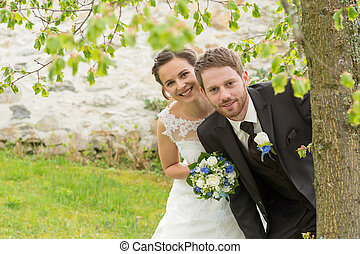 Newlyweds look of tree out - junges Brautpaar schaut freudig...