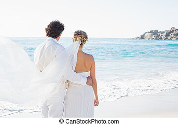 Newlyweds looking out to the sea together