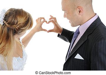 Newlyweds make heart fingers. Isolated on white