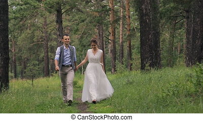 Newlyweds on photo shoot in forest walking, enjoy moments outdoors