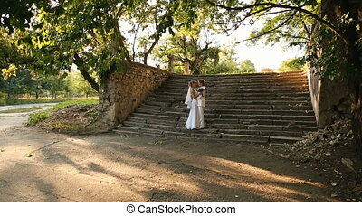 newlyweds on stairs - Happy newlyweds kissing on nature