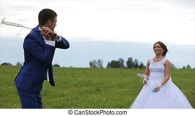 Newlyweds playing badminton on green meadow