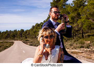Newlyweds pose in the middle of nature with vintage phones