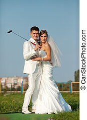 Newlyweds pose on the golf field in a sunny day
