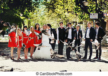 Newlyweds pose with friends on the street in a sunny day