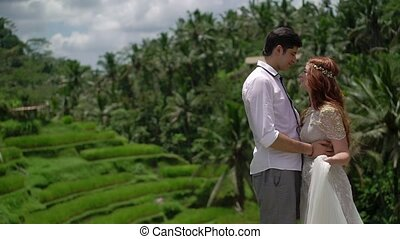 Newlyweds posing at rice terrace in Bali. Holding hands,...