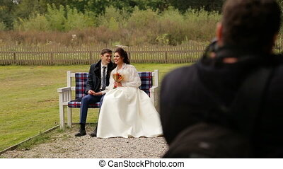 Newlyweds posing to photographer on a bench