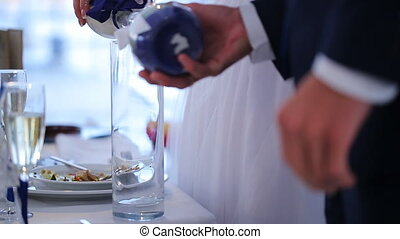 Newlyweds pour colorful sand in glass during wedding celebration. Wineglasses that are filled with sparkling shampagne stand on table near them. One by one they lay into vase their parts of marine bulk grains that symbolizes eternal union of souls for many years. Fiancee has white mass and groom has...