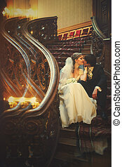 Newlyweds sits on the old wooden stairs with curved elements in the theatre