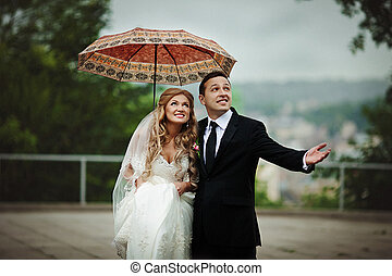Newlyweds stand under an orange umbrella waiting for the rain