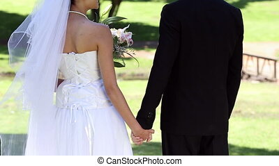 Newlyweds standing in the park holding hands