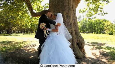 Newlyweds Standing Under A Tree