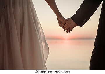 Newlyweds staying arm in arm in front of the sunset