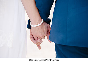 Newlyweds staying together and holding arm in arm