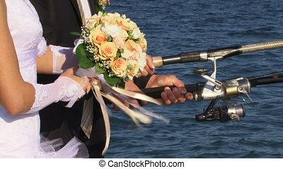 Newlyweds do fishing on the beach.