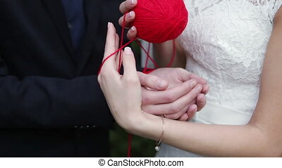Newlyweds tangle - Bride groom shakes hands woolen tangle