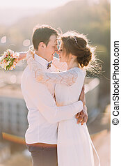 Newlyweds touch each other with noses, while bride holds  bouquet on cityscape background