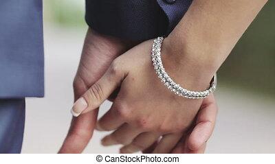 Newlyweds - Young couple holding hands, go to the Rasfokus....