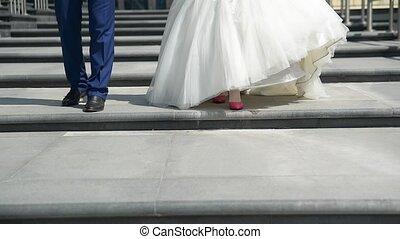 Newlyweds walk in the street, bottom view