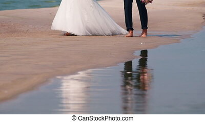 Newlyweds walking along the beach