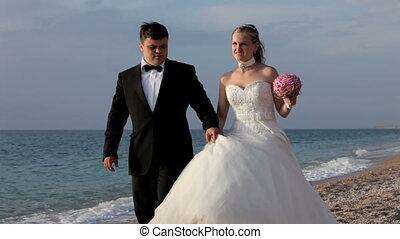 Newlyweds walking along the seashor