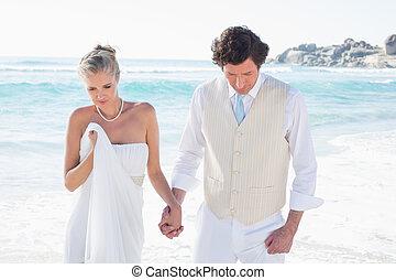 Newlyweds walking hand in hand