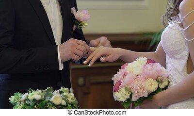 Newlyweds wearing wedding rings on ceremony closeup