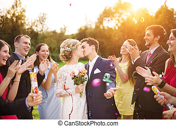 Newlyweds with guest on their garden party - Full length...