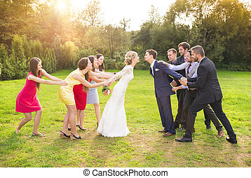 Newlyweds with guest posing in park - Funny portrait of...