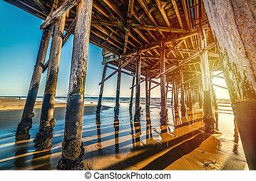 Newport Beach wooden pier seen from the ground at sunset