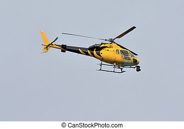 News Helicopter - A black and yellow helicopter on blue sky...