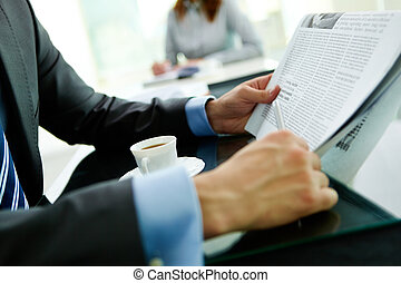News - Close-up shot of a businessman reading the latest...