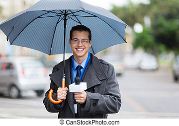 male news reporter holding umbrella and live broadcasting in the rain