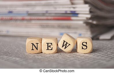 news - the word news on cubes on a newspaper