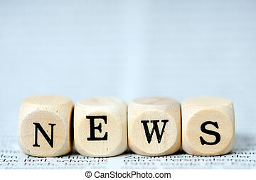News - Wooden dice with the word news on a newspaper
