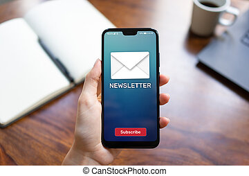Newsletter subscription button on mobile phone screen. Business marketing concept.