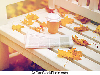 newspaper and coffee cup on bench in autumn park - season...