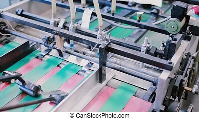 Newspapers in the process of publishing with sound. Printing establishment detail on production line with sound.