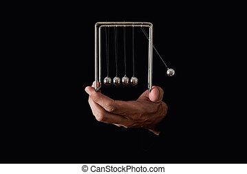 Newton's pendulum or cradle in human hands on dark background