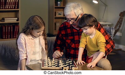 Next Step - Little girl playing chess with her granddad...