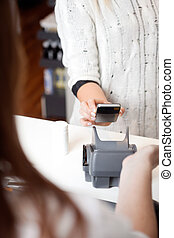 NFC Payment Using Mobile Phone - Detail of woman paying for...